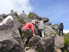 日光白根山の頂上の岩場を慎重に登る